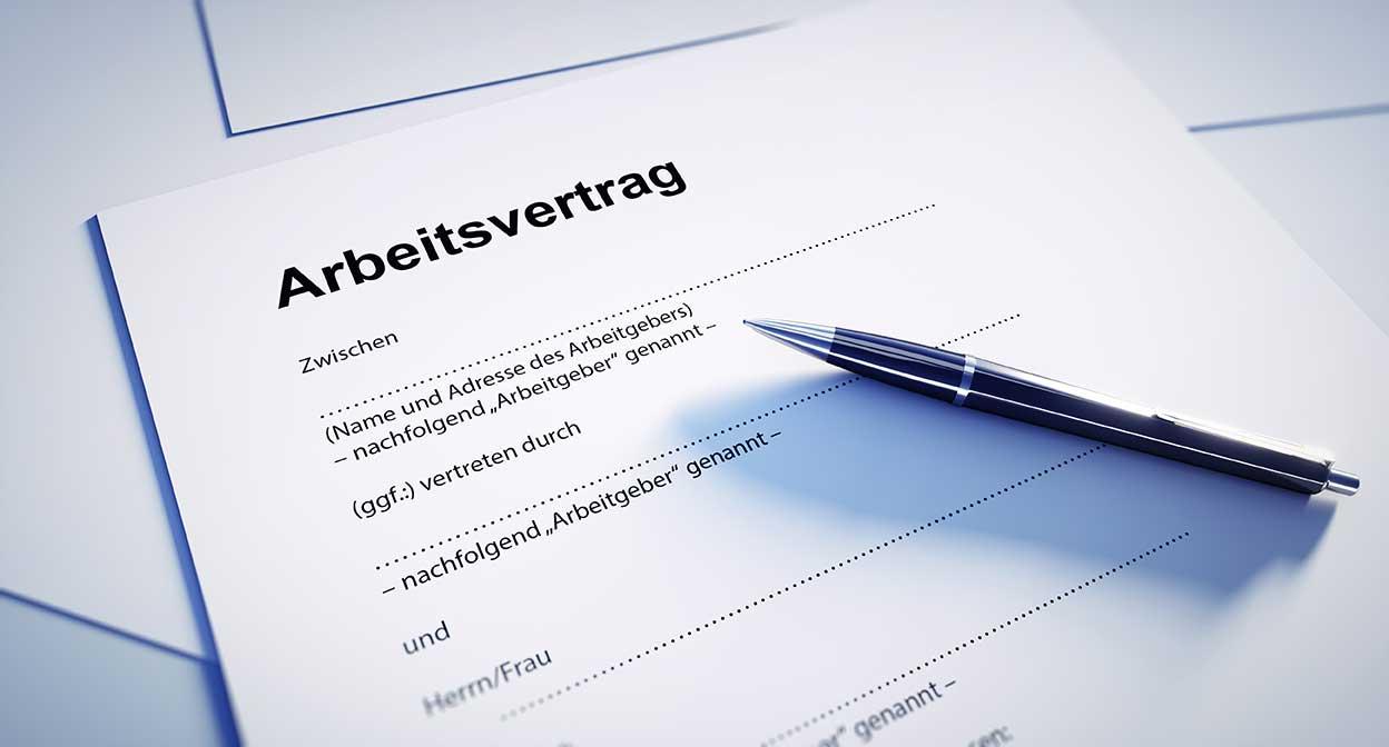 AltText: Ein Arbeitsvertrag liegt auf einem Tisch und darauf ein Stift.