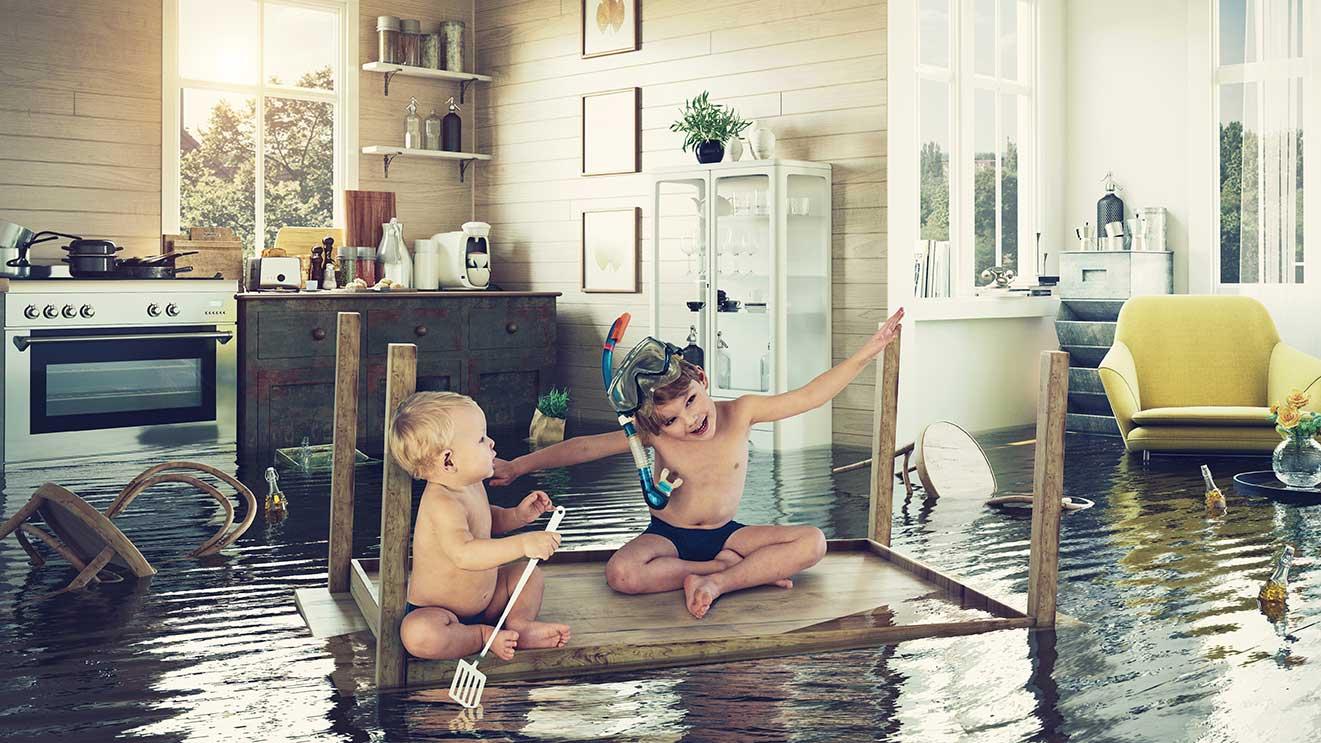 AltText: Kinder schwimmen auf einem Tisch durch die überflutete Wohnung.