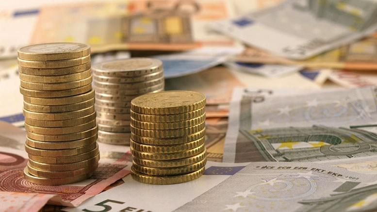 AltText: Gestapelte Euromünzen und Geldscheine liegen auf einem Tisch.