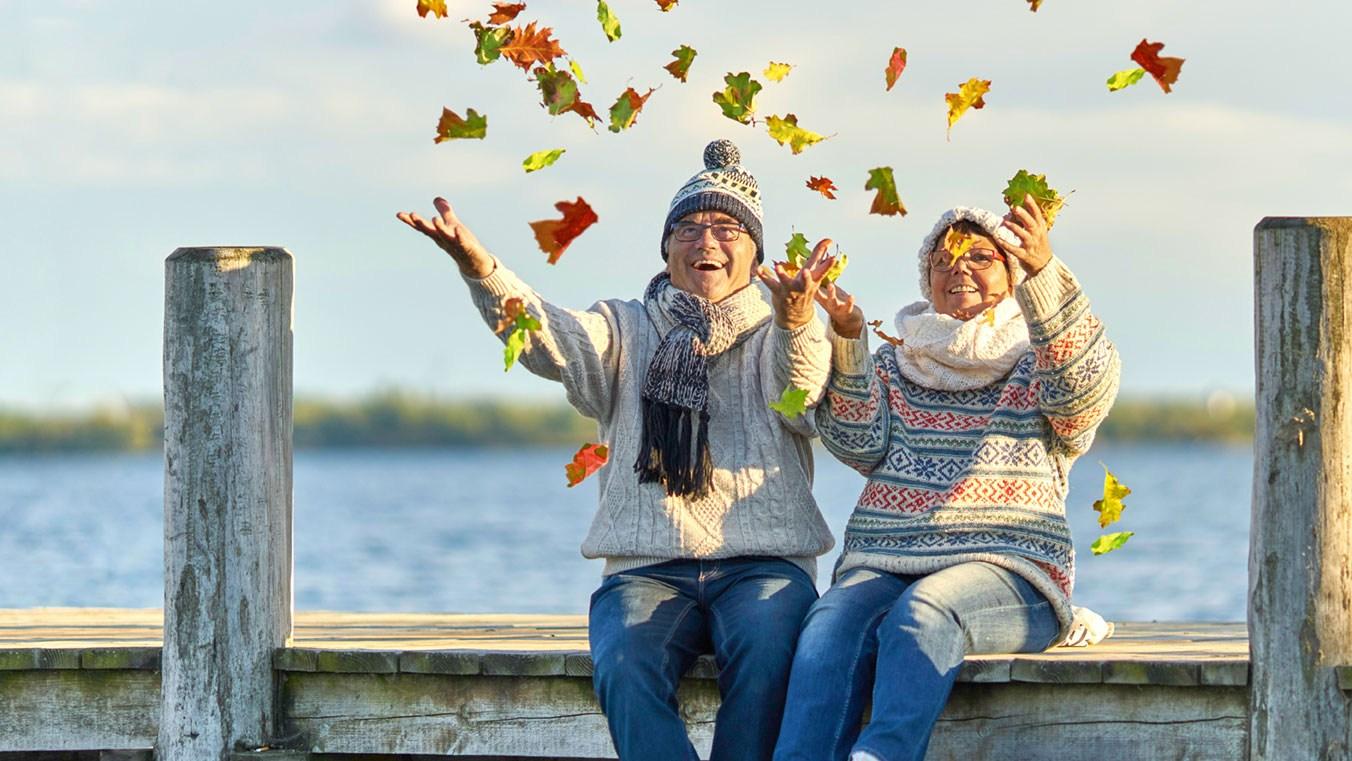 AltText: Ehepaar sitzt auf einem Steg und wirft Laubblätter in die Luft