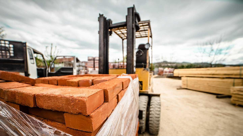 AltText: Ein Bagger fährt auf eine Baustelle Ziegelsteine herum.