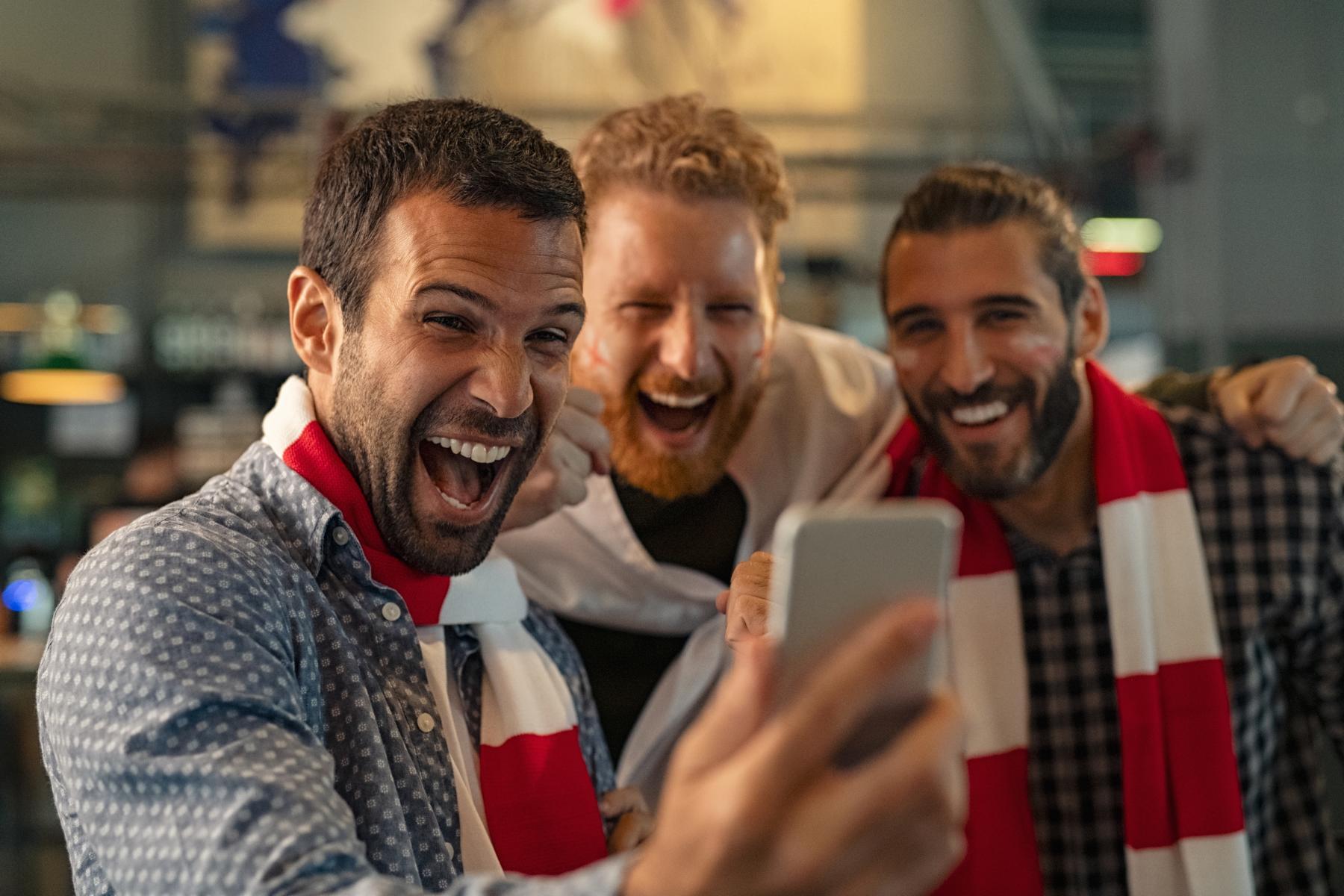 AltText: Drei Männer blicken auf das Smartphone und freuen sich das Glücksspiel.