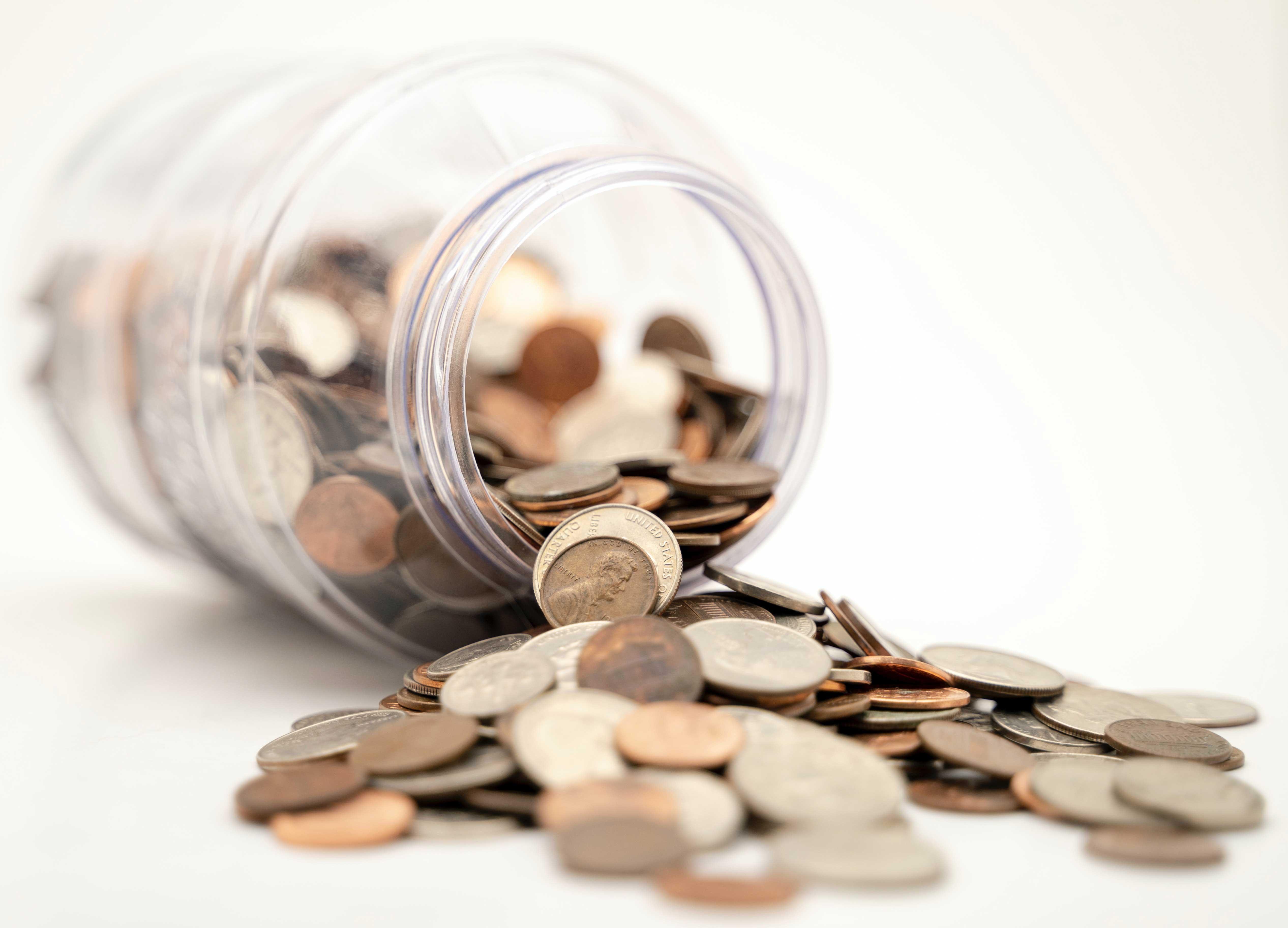 AltText: Ein umgefallenes Glas mit Kleingeld.