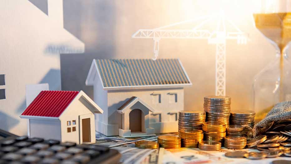 AltText: Ein Taschenrechner, zwei Miniaturhäuser sowie Münzen und eine fließende Sanduhr werden als Symbole der Immobilienfinanzierung genutzt.