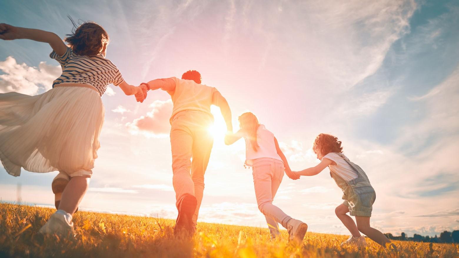 AltText: Adoption innerhalb der Familie: Adoptiv-Vater und Kinder spielen auf einer Wiese