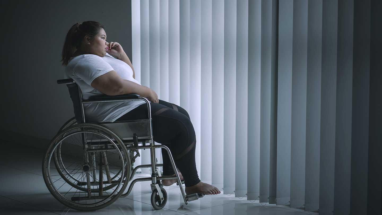 AltText: Eine Arbeitnehmerin mit Schwerbehinderung sitzt im Rollstuhl vor dem Fenster