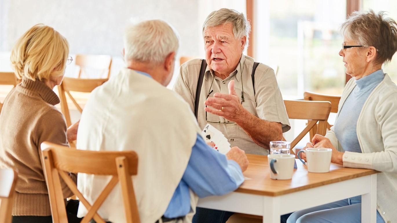 AltText: Vier Senioren sitzen an einem Tisch. Sie trinken Kaffee und spielen Karten