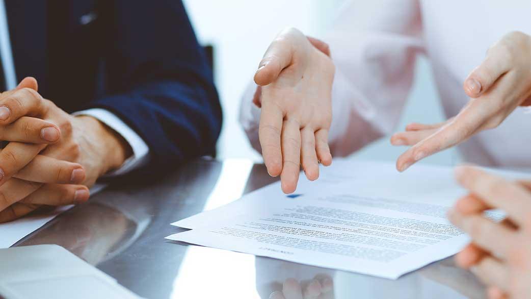 AltText: Erblasser und Erbe sind beim Notar und setzen am Tisch Erbvertrag auf