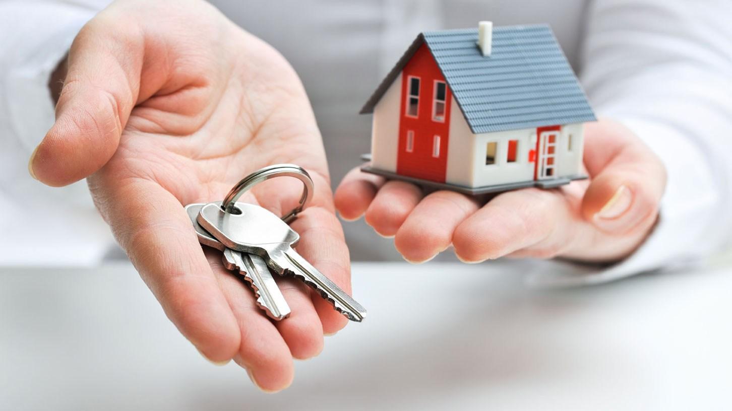 AltText: Ein Schlüssel und ein Miniaturhaus in jeweils einer Hand