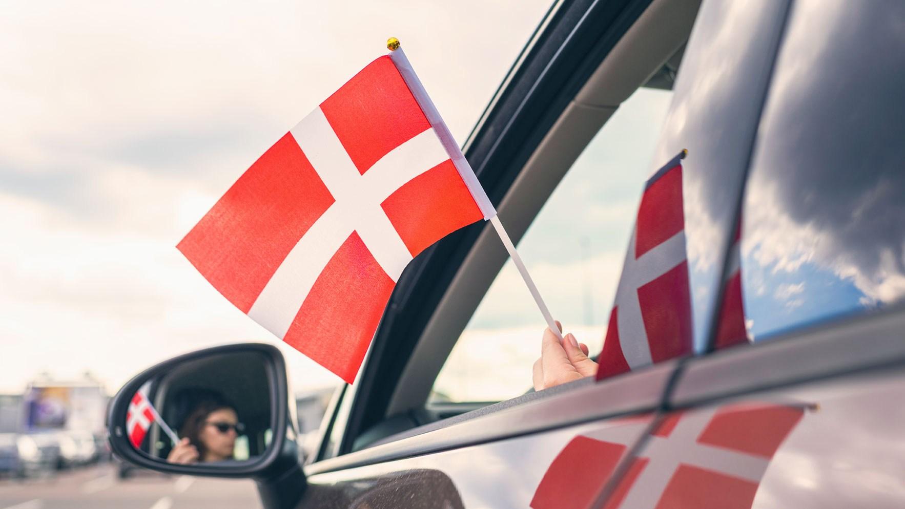 AltText: Autofahrerin mit dänischer Flagge