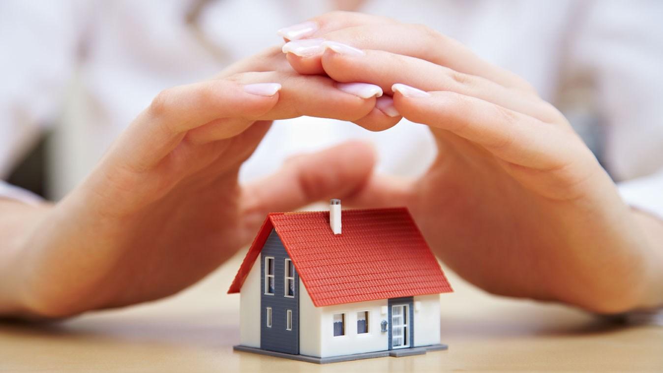AltText: Hände überdecken ein kleines Spielzeughaus.