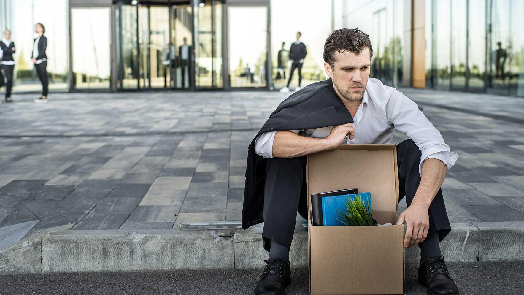 AltText: Ein Mann sitzt am Boden. Neben ihm steht ein Karton mit Büroartikeln. Er hält ein Kündigungsschreiben in der Hand.