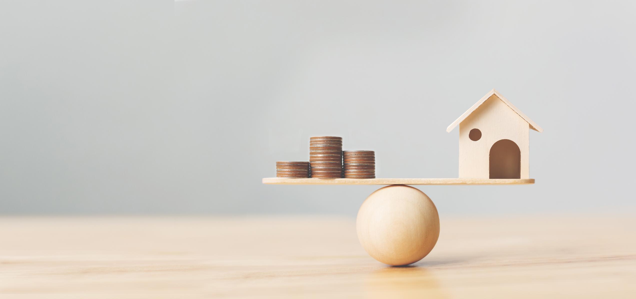 Ein Haus und Geld sind in der Waage ausgerichtet.