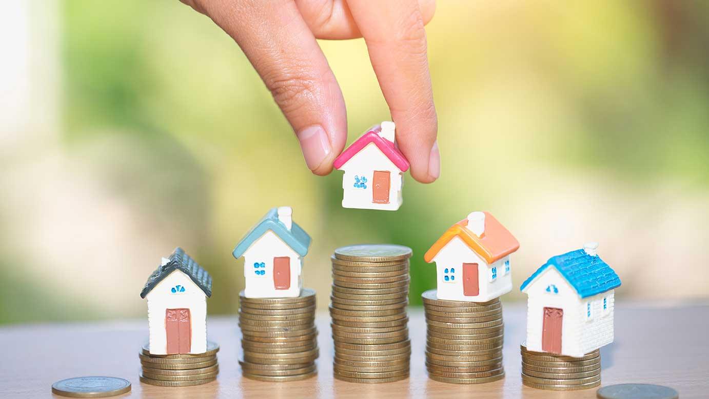 AltText: Kleine Häuser werden auf Münzstapel gestellt.